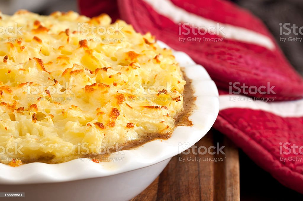 Close-up of warm, baked shepherds pie with red potholder stock photo