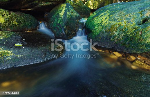Close-up of water flowing through pebbles in stream