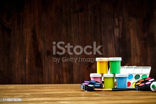Back to school themes. Close-up of watercolor paint sets and paintbrushes on desk with copy space