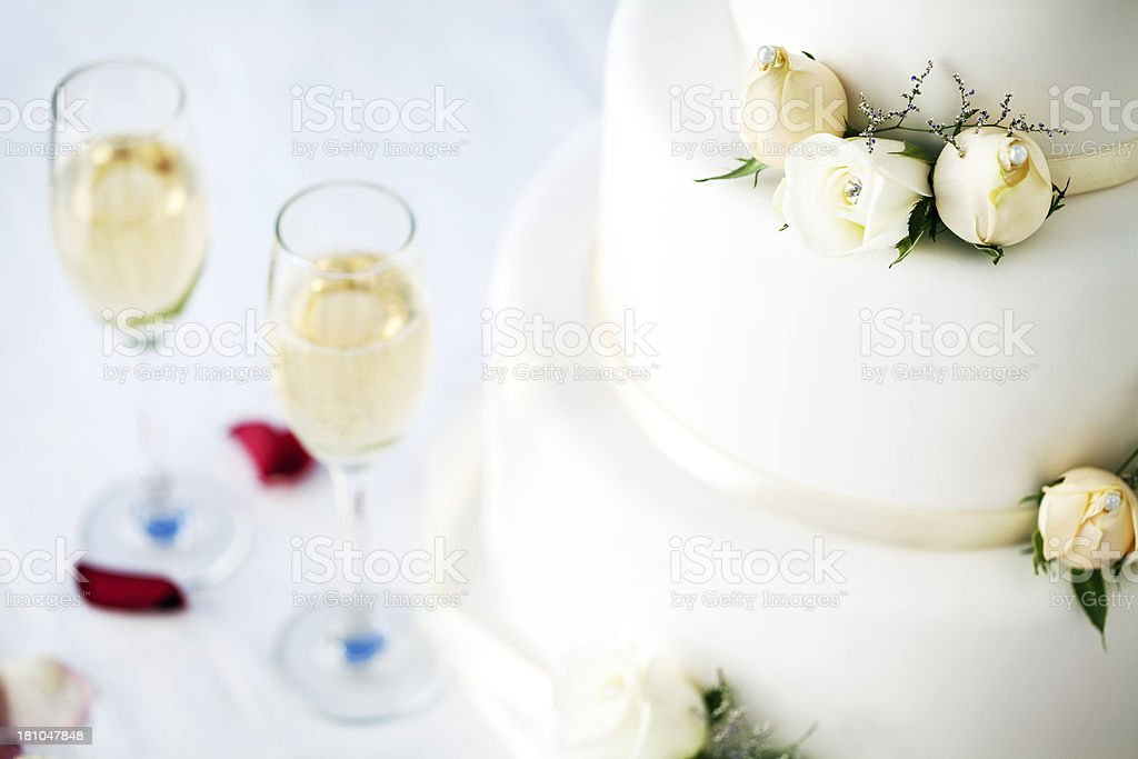 Close-Up Of Wedding Cake And Champagne Flutes On Table royalty-free stock photo