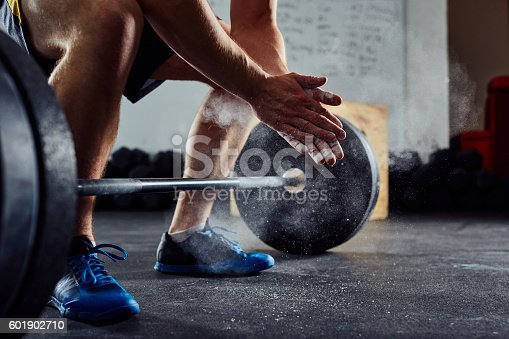 istock Closeup of weightlifter clapping hands before  barbell workout a 601902710