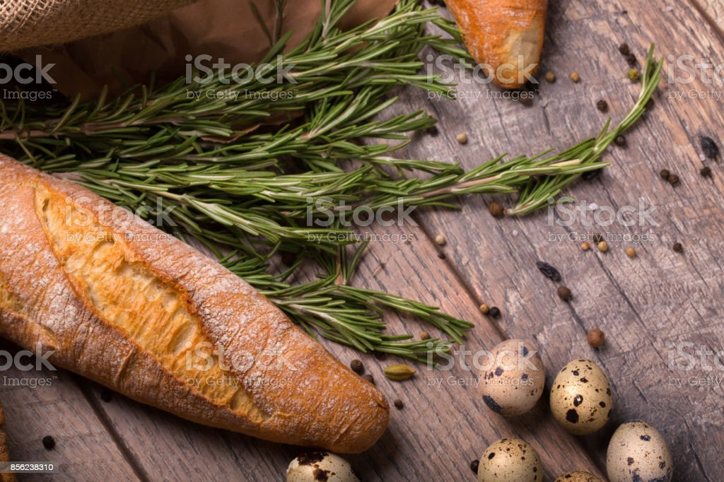 Closeup of wheat baguette, twigs of fragrant rosemary, speckled quail eggs, seasonings on a light wooden background. stock photo