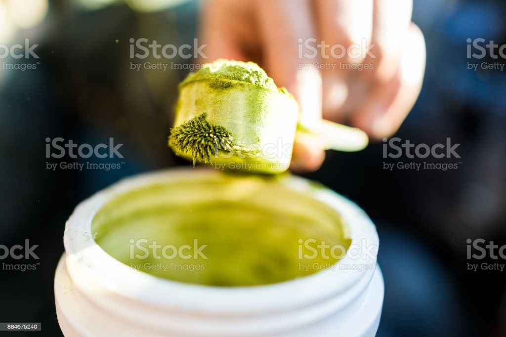 Closeup of wheatgrass powder crystals with static magnetic cling structure on plastic spoon macro with jar, hand holding scooping stock photo
