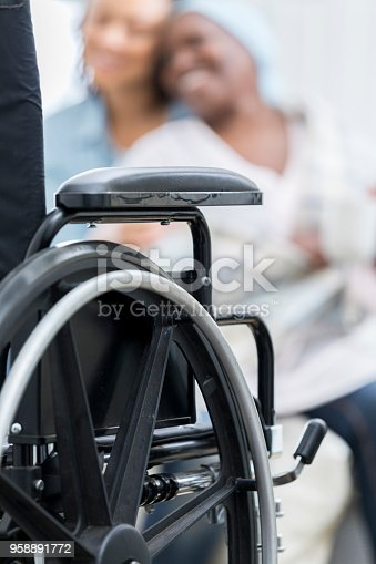 932074776 istock photo Closeup of wheelchair with patient in the background 958891772