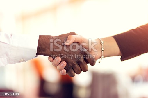 istock Closeup of White and Black shaking hands over a deal 918730008