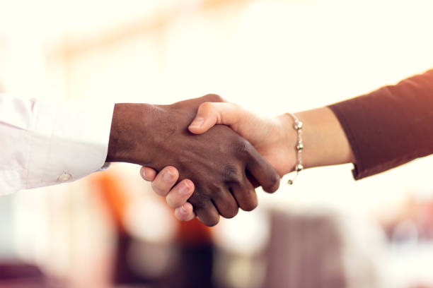 closeup of white and black shaking hands over a deal - handshake stock pictures, royalty-free photos & images