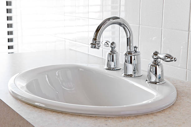 Close-up of white bathroom vanity with silver faucet stock photo