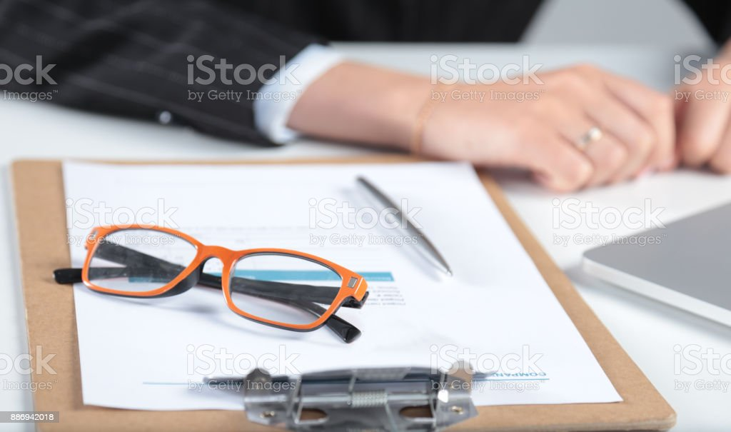 Closeup of white desktop with glasses, notepads, pen and other items. Selective focus. stock photo