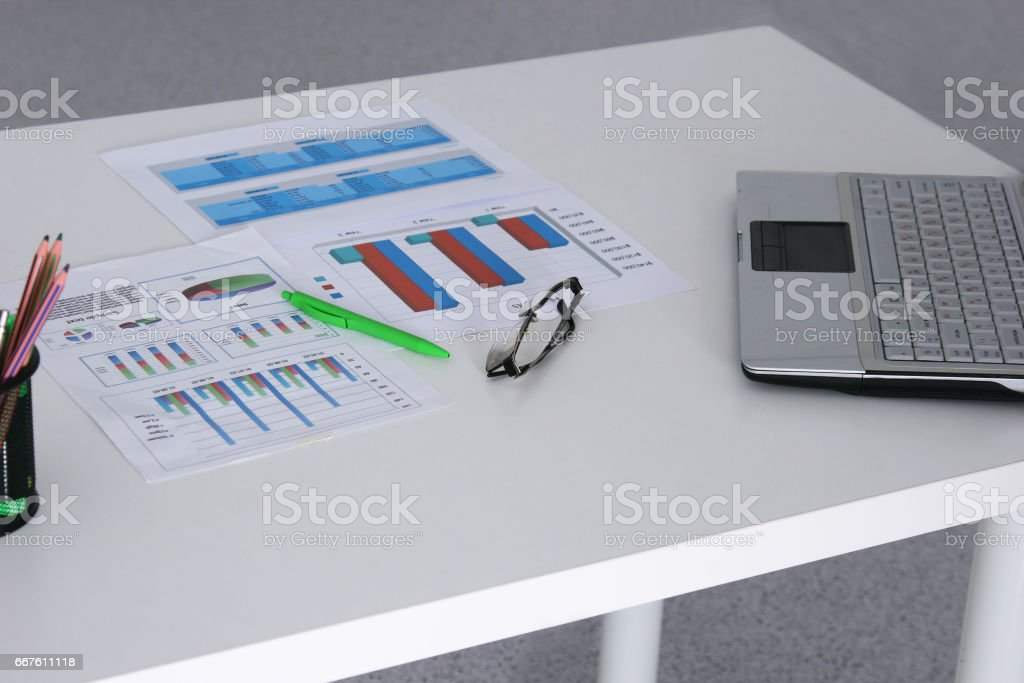 Closeup of white desktop with laptop, glasses, coffee cup, notepads and other items on blurry city background stock photo