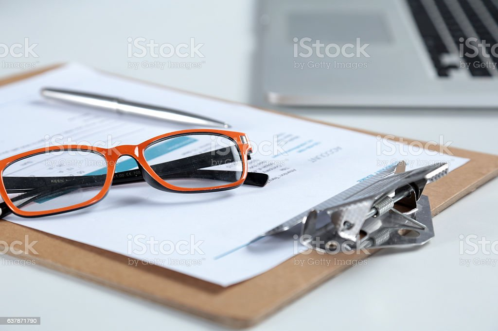 Closeup of white desktop with laptop, glasses, coffee cup, notepads stock photo