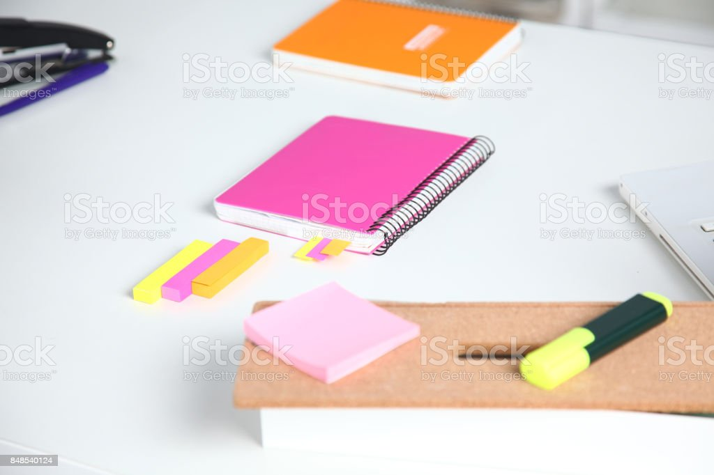 Closeup of white desktop with notepads, pen, coffee cup and other items. Selective focus. stock photo