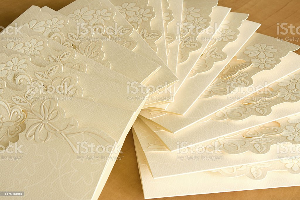 Close-up of white invitation cards with engraved flowers stock photo