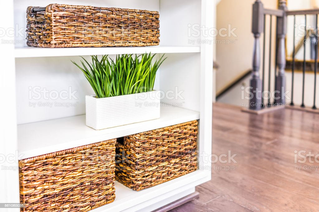 Closeup of white, modern, minimalist shelves in kitchen or living room with woven baskets and green plants pots, containers stock photo