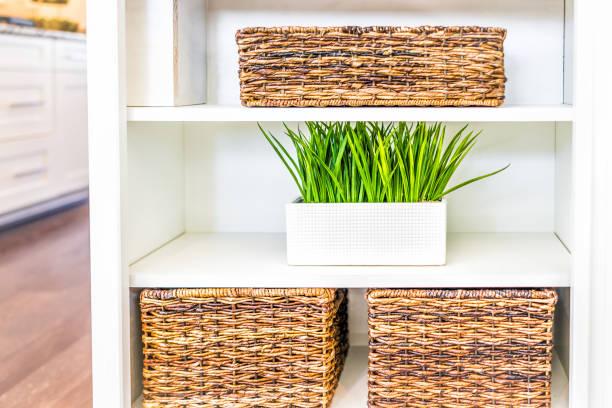 nahaufnahme von weiß, modern, minimalistisch regale in küche oder wohnzimmer mit geflochtenen körben und grünen pflanzen töpfe, behälter - küchenorganisation stock-fotos und bilder