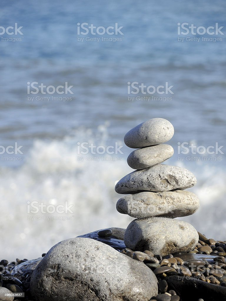 Close-up of white pebbles stack over blue sea. stock photo