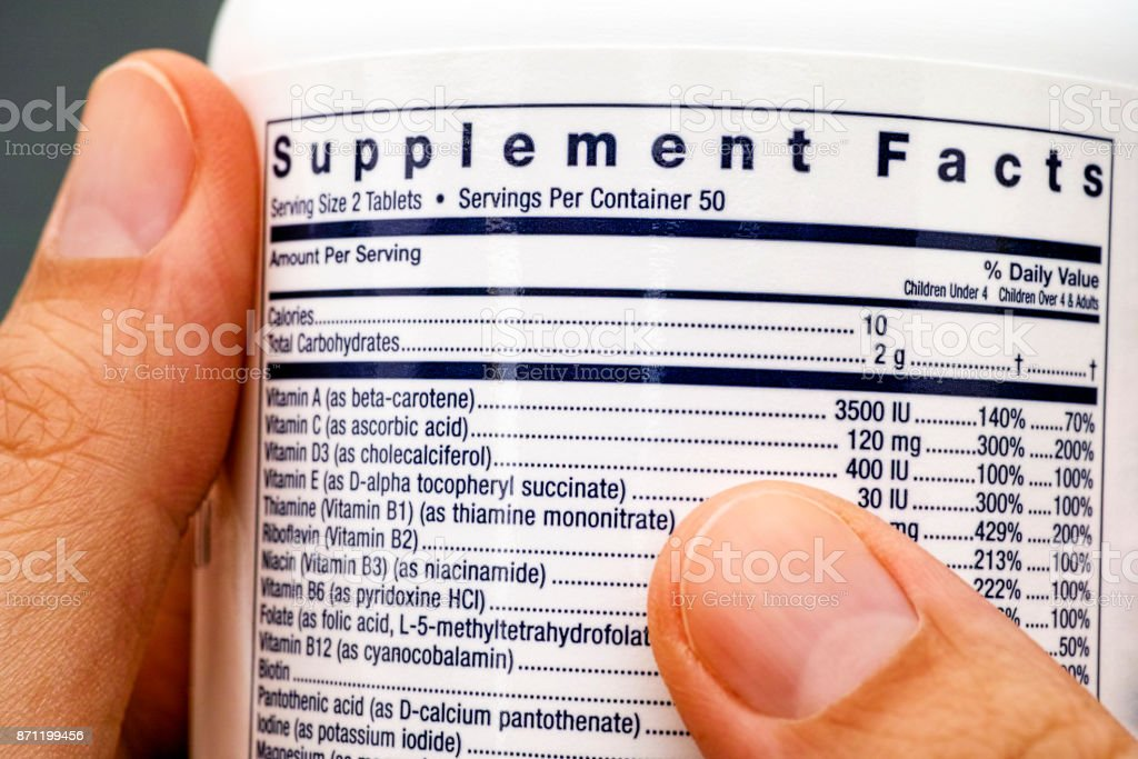 Close-up of white plastic jar with supplement facts of multivitamins in woman hands. stock photo