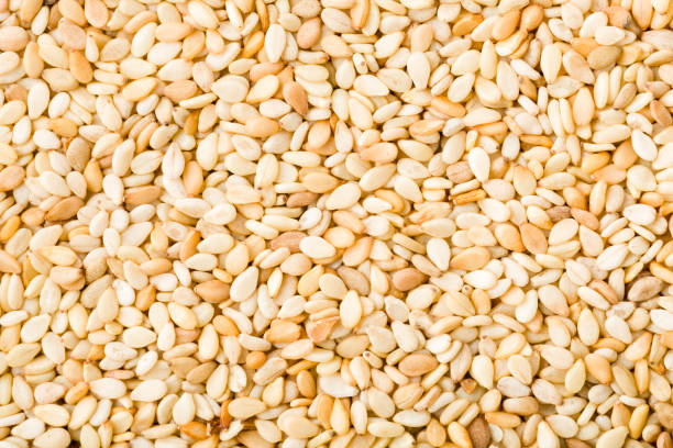 closeup of white sesame seeds background - sesame stock photos and pictures