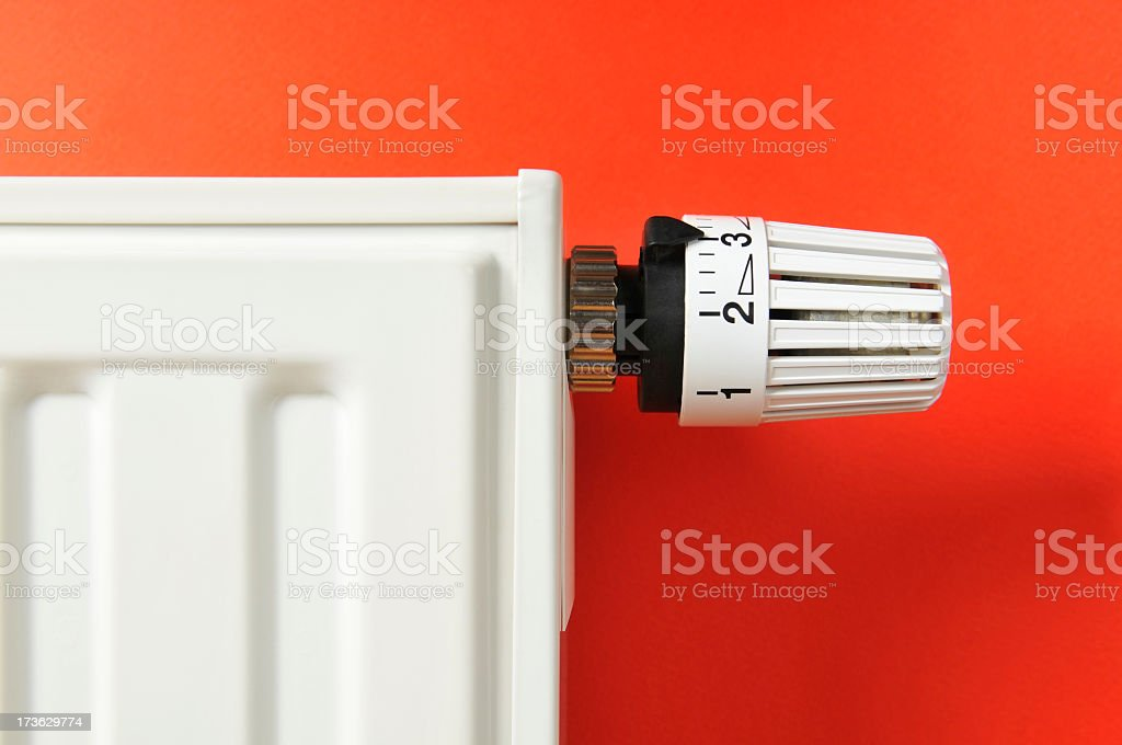 Close-up of white thermostat and radiator on red background stock photo