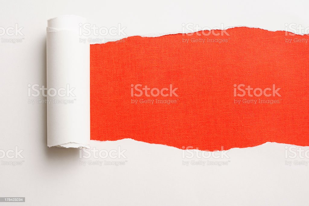 Close-up of white torn paper on orange background. stock photo