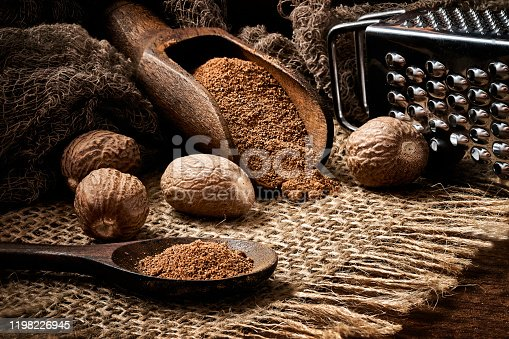 Close-up of whole nut and nutmeg powder in a wooden spoon with  on burlap and rustic table