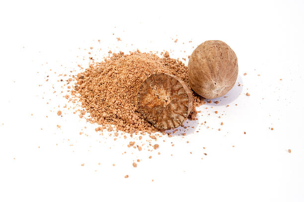 A close-up of whole nutmeg and crushed nutmeg Whole and grated nutmeg isolated on white background nutmeg stock pictures, royalty-free photos & images