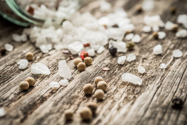 Closeup of whole peppercorns and crystal sea salt on rustic wood as background stock photo