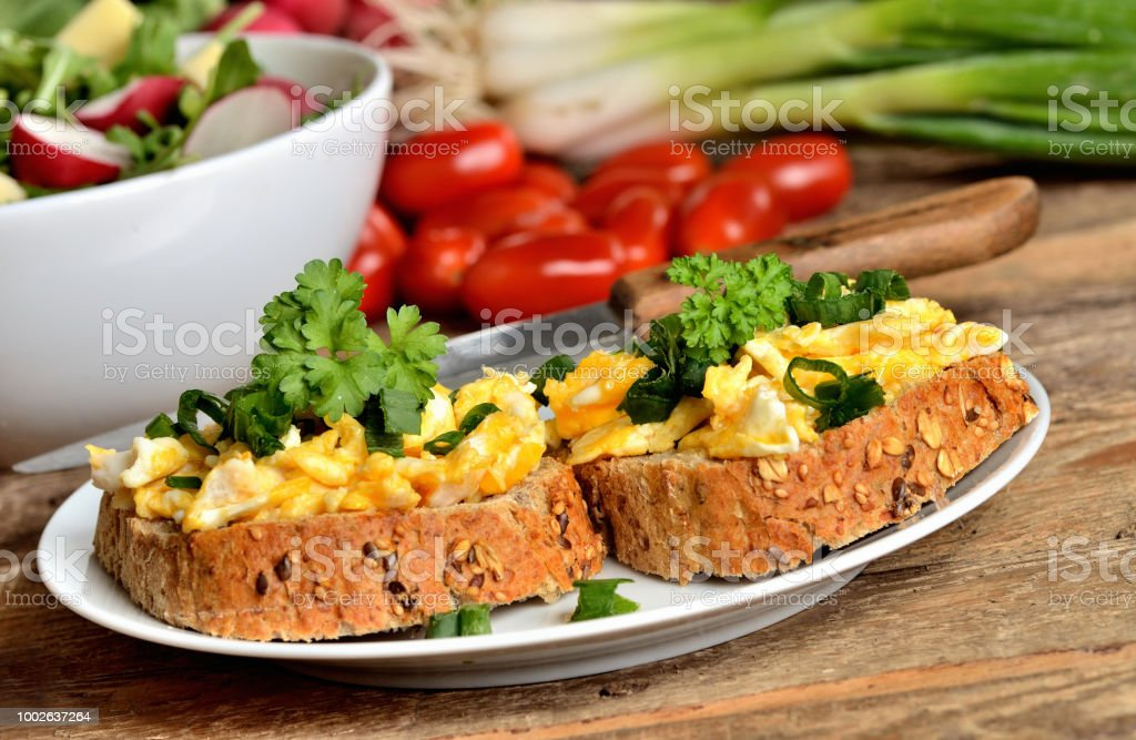 Close-up of wholemeal bread with scrambled eggs, fresh herbs, spring onions, tomatoes and salad bowl in background - healthy breakfast stock photo
