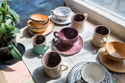 Close-up of window-sill with potted plant and various multicolored ceramic cups with dishes