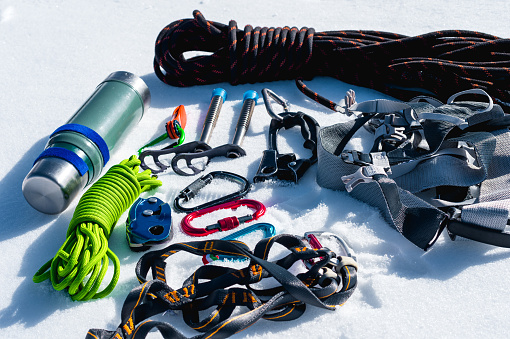 Close-up of winter climbing equipment on fresh snow on a sunny day. Carbines with a rope gazebo and zhumar as well as other adaptations when practicing winter mountaineering. Year-round ascents to snowy peaks.
