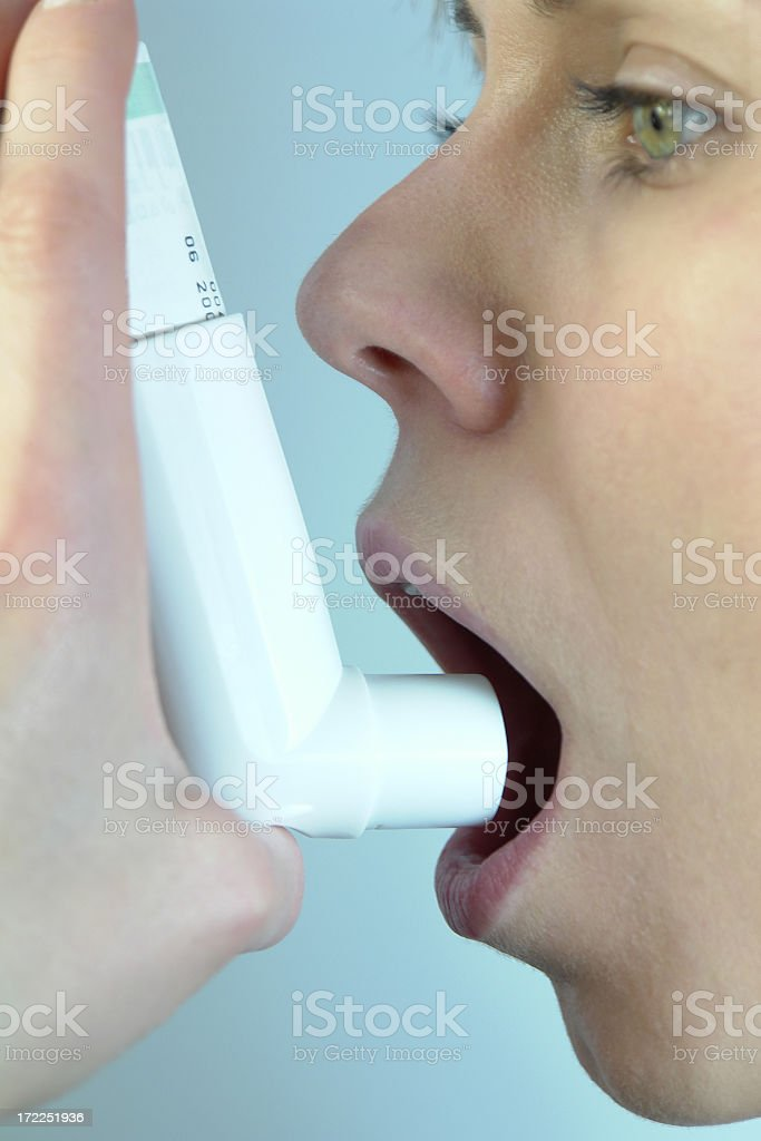 Close-up of woman, Asthma Inhaler in hand, puffs against asthma royalty-free stock photo