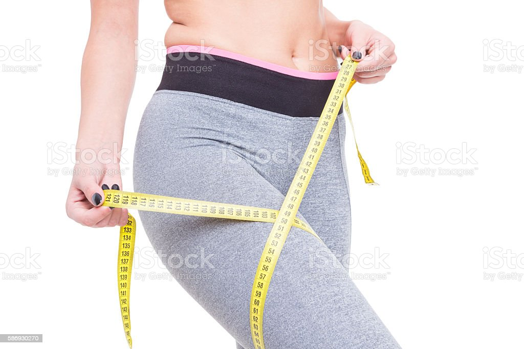 Close-up of woman at gym measuring her thigh stock photo