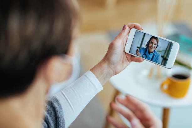 Close-up of woman communicating with her doctor via video call. stock photo