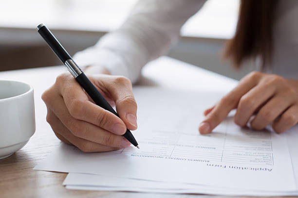 closeup of woman completing application form - applications stock photos and pictures