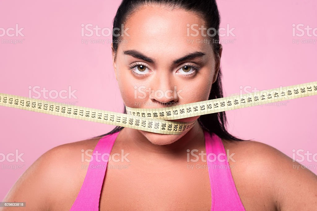 Close-up of mulatto woman covering mouth with measuring tape - Photo