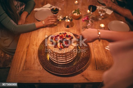 istock Close-up of woman cutting gourmet dessert at rustic dinner party 907966988