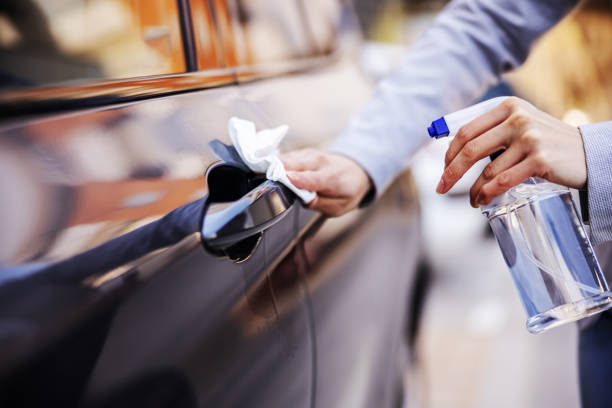 Closeup of woman disinfecting door lock on her car to prevent spreading corona virus. stock photo
