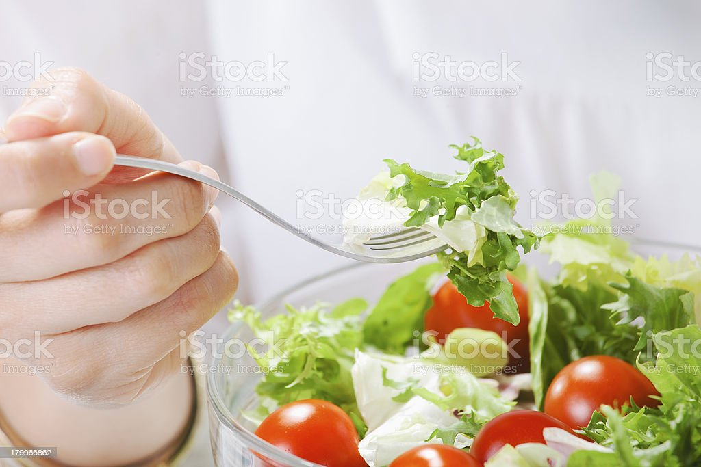 Closeup of woman eating a salad in office. royalty-free stock photo