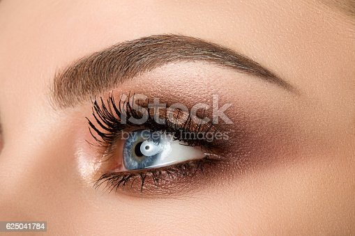 istock Close-up of woman eye with beautiful brown smokey eyes makeup 625041784