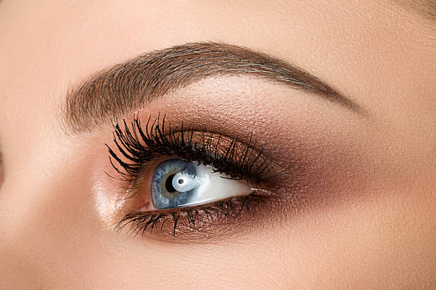 Close-up of woman eye with beautiful brown smokey eyes makeup Close up of blue woman eye with beautiful brown with red and orange shades smokey eyes makeup. Modern fashion make up. toned image stock pictures, royalty-free photos & images