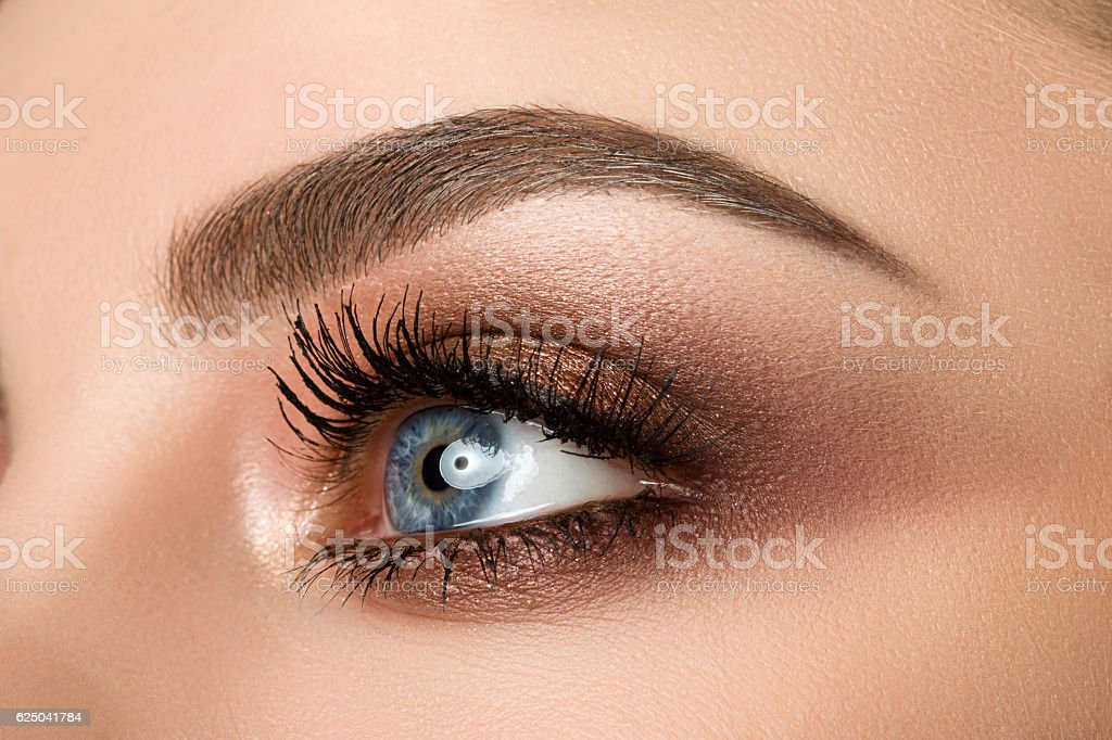 Close-up of woman eye with beautiful brown smokey eyes makeup stock photo