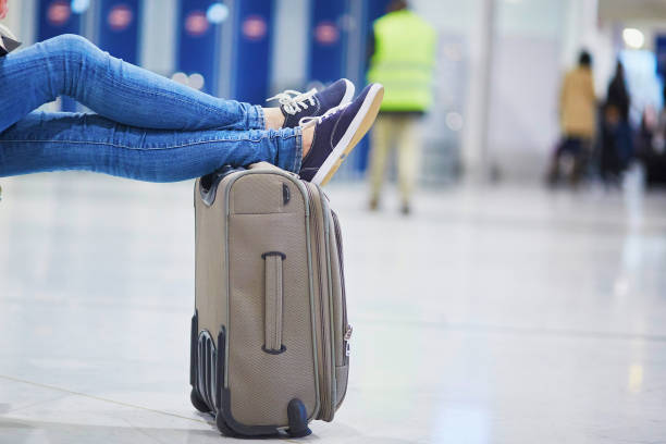 Closeup of woman feet on a suitcase in international airport Closeup of woman feet on a suitcase in international airport. Delayed or canceled flight concept carry on luggage stock pictures, royalty-free photos & images
