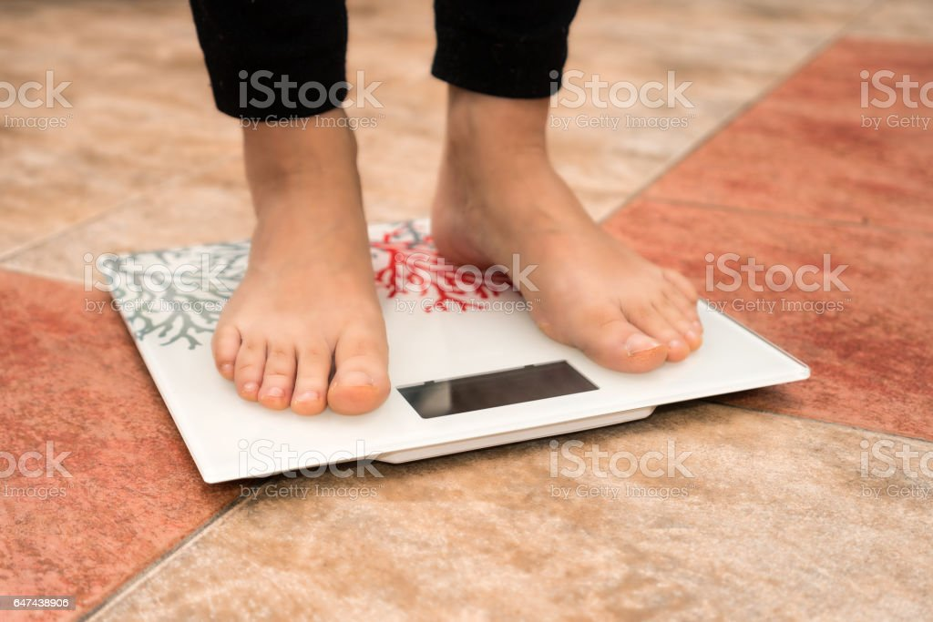 close-up of woman feet weighing in bathroom stock photo