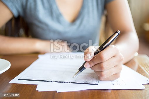 istock Close-up of woman filling application form 687128082
