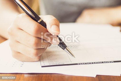 istock Close-up of woman filling application form 839040054