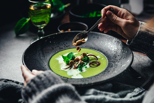 Close-up of woman garnishing green peas and cream soup. Female hand adding roasted garlic to vegan soup on table.