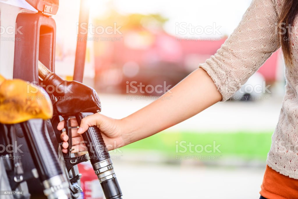 Closeup of woman  hand holding a fuel pump at a station. stock photo