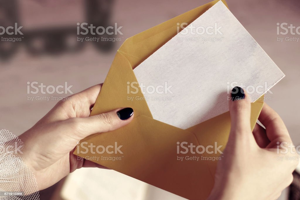 Closeup of Woman Hand Opening Envelope with Mockup Business Card or Blank Letter with Copyspace stock photo