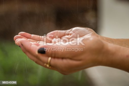 Hands catching clean falling rain drops close up. Environmental and healthcare concept.