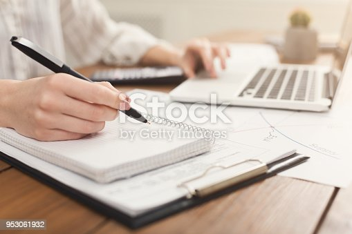 Closeup of woman hands typing on laptop and counting on calculator. Financial background, count and pay an account, copy space, selective focus