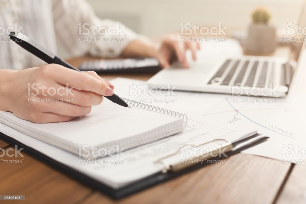 Closeup of woman hands typing on laptop and counting on calculator stock photo